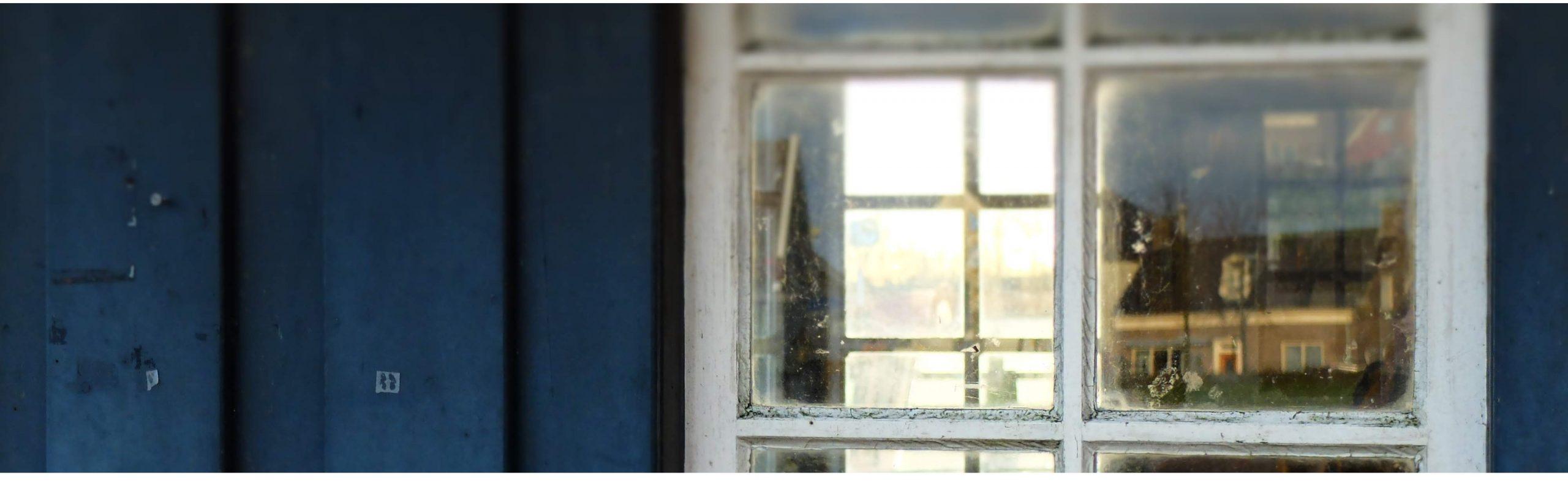 Blick durch ein weißes Fenster in einer blauen Holzfassade in das Innere eines Esszimmers